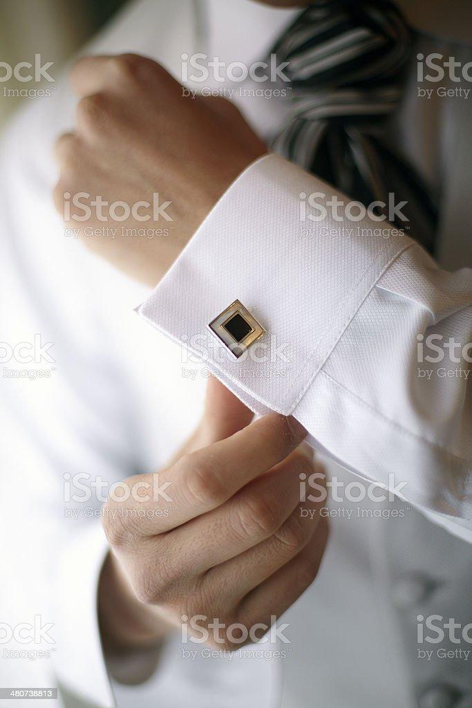 Novio anudar un elegante cufflink en su boda camisa - foto de stock
