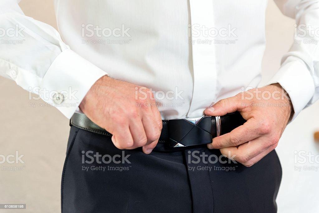 Groom tying belt stock photo