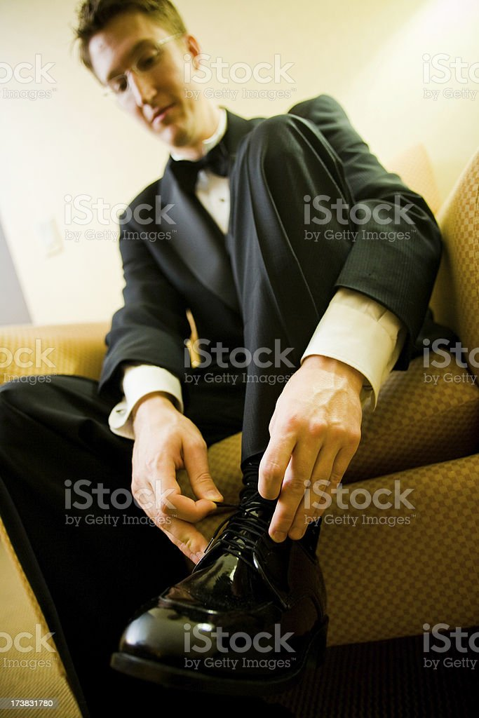 groom tying his shoes stock photo