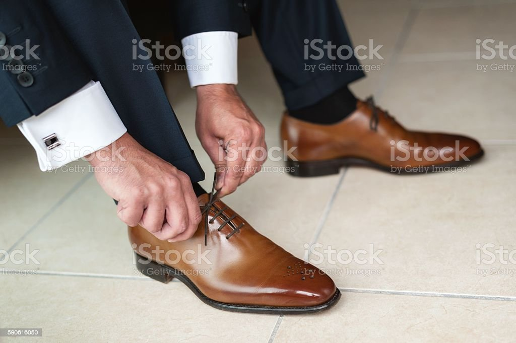 Groom tying up shoes stock photo