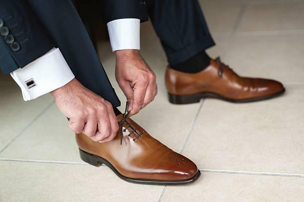 groom tying up shoes - hochzeitsanzug herren stock-fotos und bilder