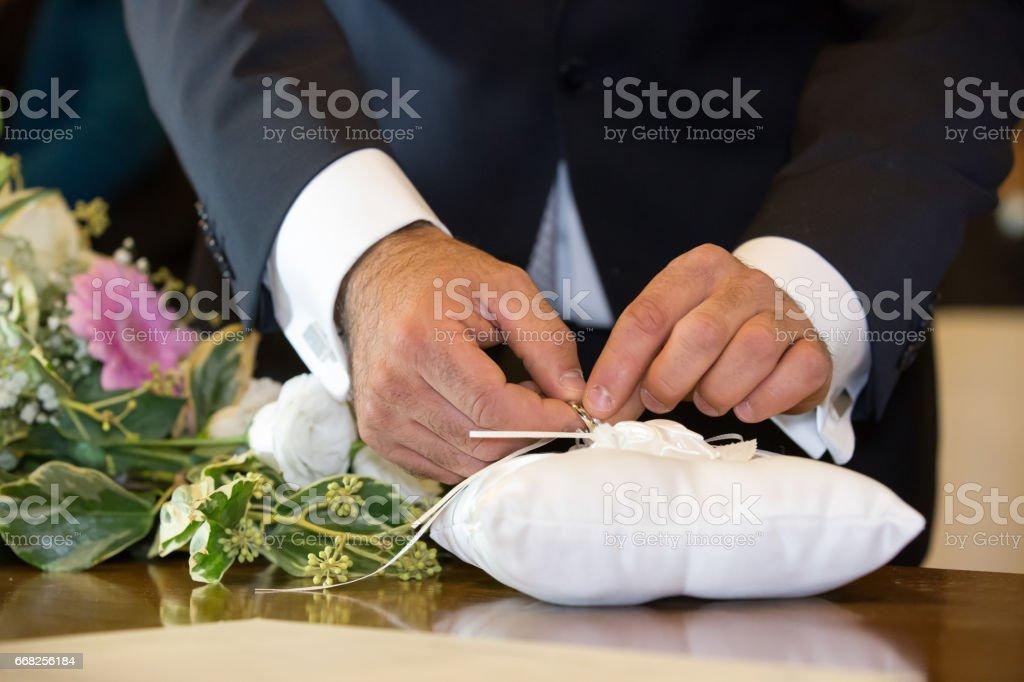 Groom untying rings, particular foto stock royalty-free