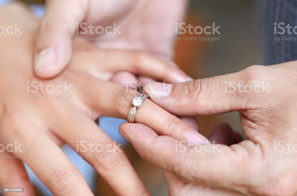 Groom wears ring on bride's finger. Selective focus at wedding ring. stock photo