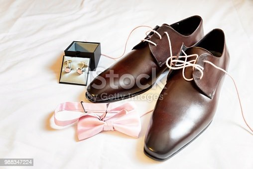 Horizontal color image of wedding preparation - groom accessories arranged on bed - cufflinks in box, light pink bow tie, brown leather shoes - all in pink style.
