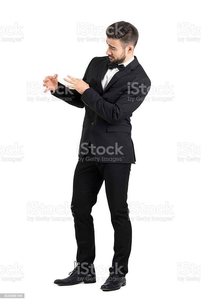 Groom with funny expression putting wedding ring on his finger stock photo