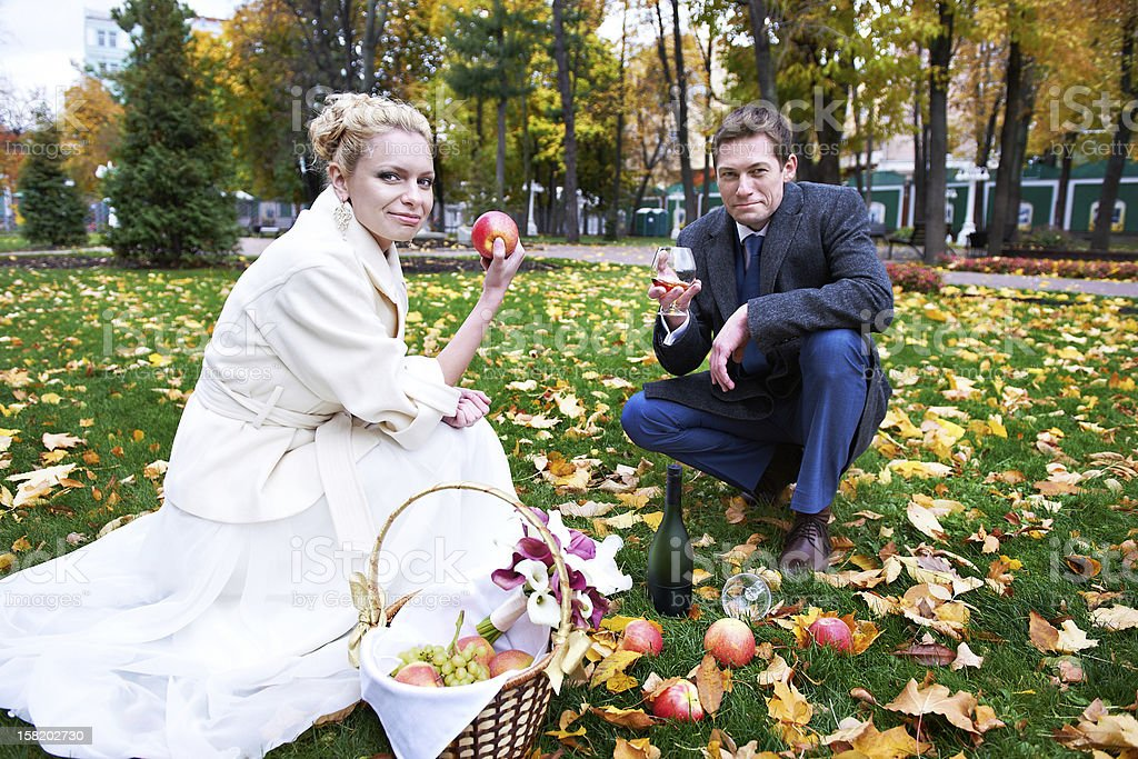 Groom with glass of brandy, and bride eat red apple Groom with glass of brandy, and bride with red apple on wedding walk Adult Stock Photo