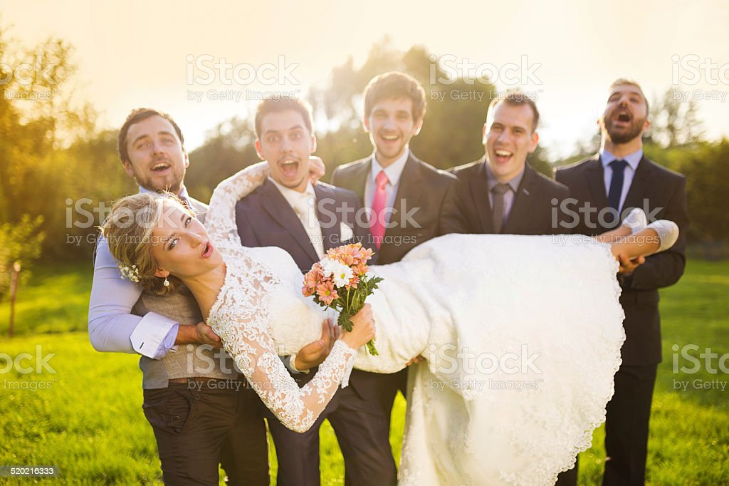 Groom with his friends holding bride stock photo