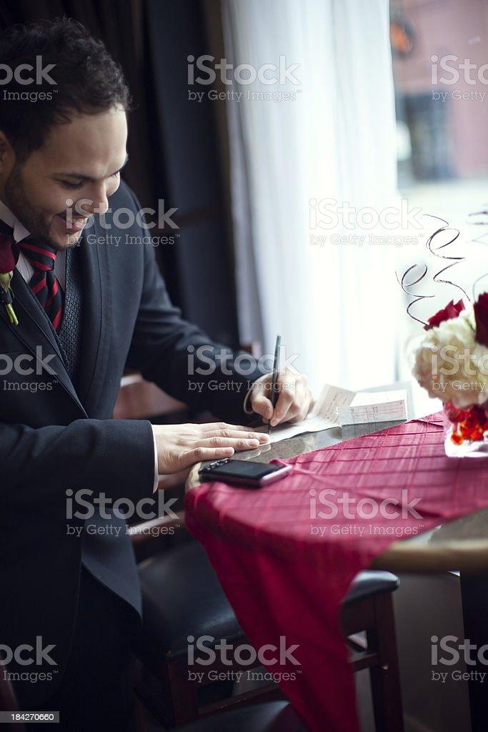 Groom Writes Checks for Wedding Payment stock photo