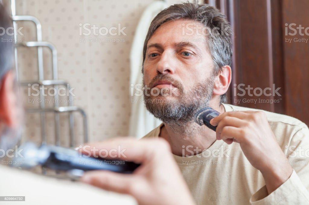 Grooming beard. Man alone shears beard in bathroom stock photo