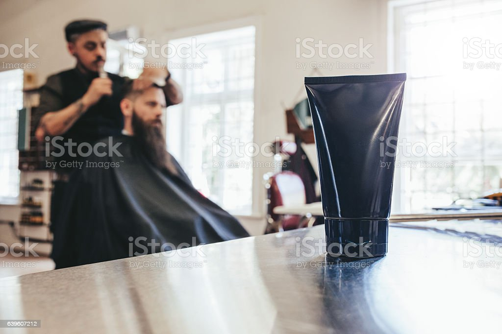 Grooming product at salon with barber cutting hair of a man. Focus on...