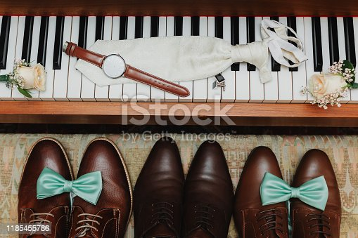 Groom's accessories. Stylish watch, tie, boutonniere and cufflinks on the keys for piano. The bridegroom's shoes with blue tie on them stand near the piano. Groom's morning.