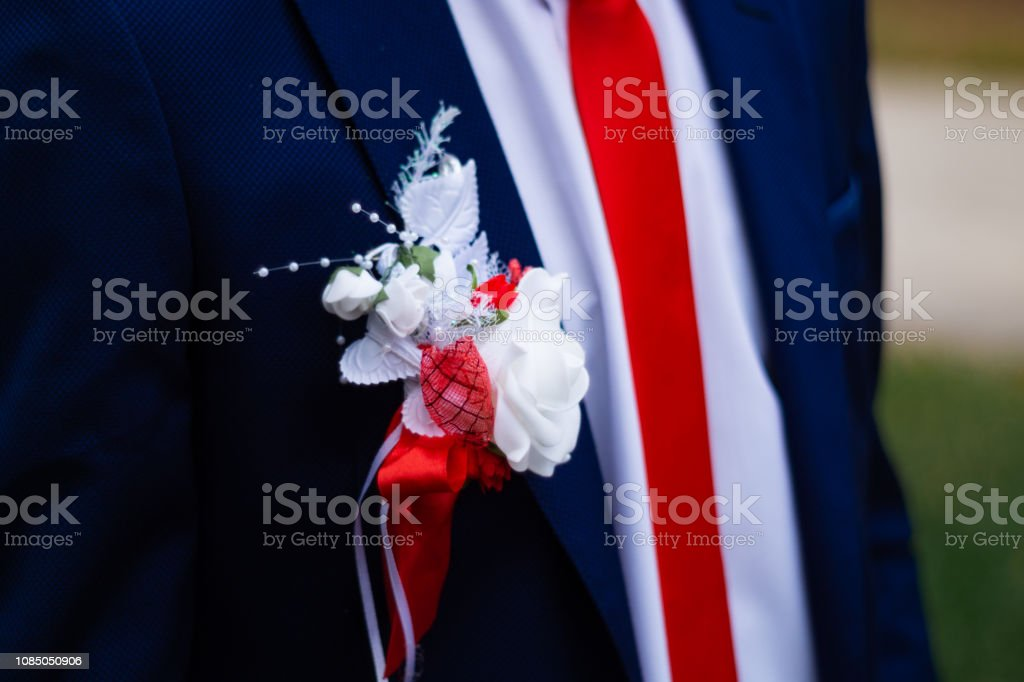 Groom\'s suit with a flower on his chest. Wedding details in close-up...