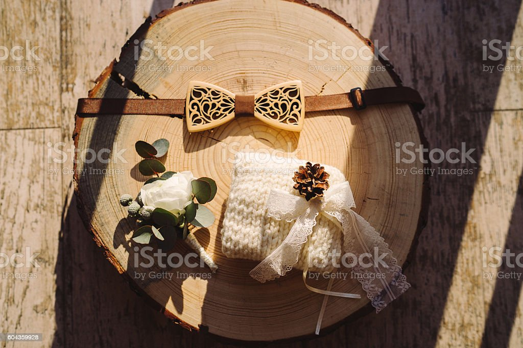 groom's wooden bow tie, boutonniere and rings pillow stock photo
