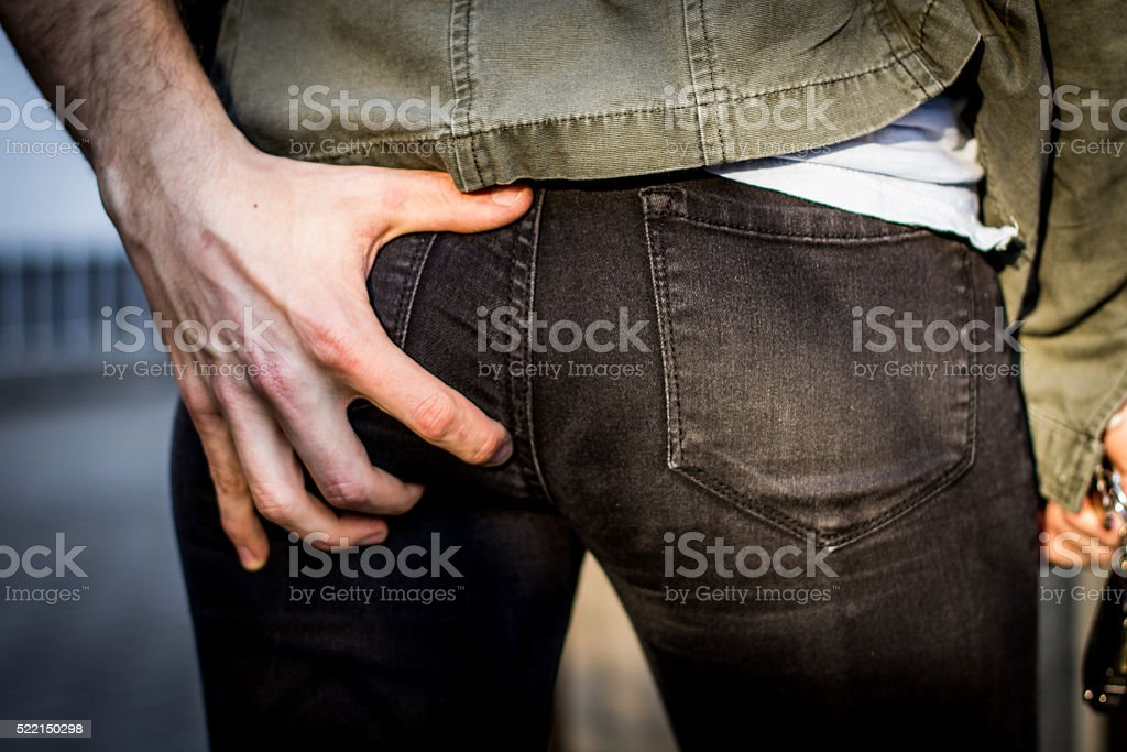 Groping Hand grabs woman's butt in public and harassing her stock photo