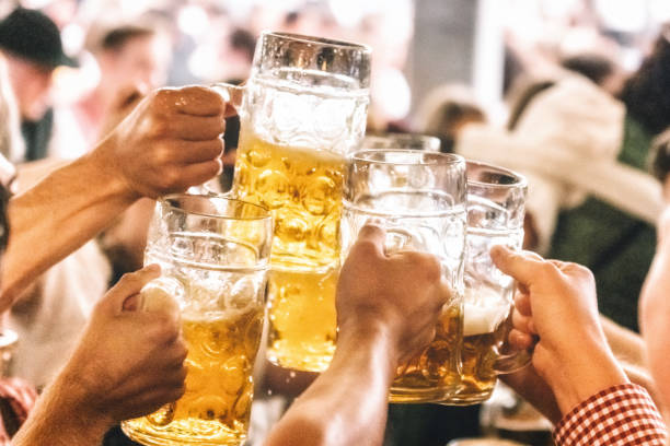 gropup of people clinking mass-beer glasses at oktoberfest in munich stock photo