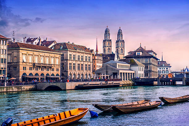 Grossmunster Cathedral with River Limmat in Zurich at Sunset Beautiful Zurich Cityscape. Grossmunster Cathedral with River Limmat, traditional Swiss buildings at sunset. Zurich, Switzerland. zurich stock pictures, royalty-free photos & images