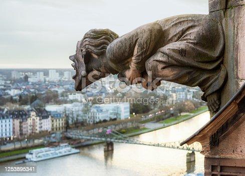 istock Grotesque gargoyle screaming over the city 1253895341