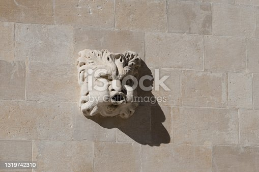 istock Grotesque stone head sculpture on the wall 1319742310