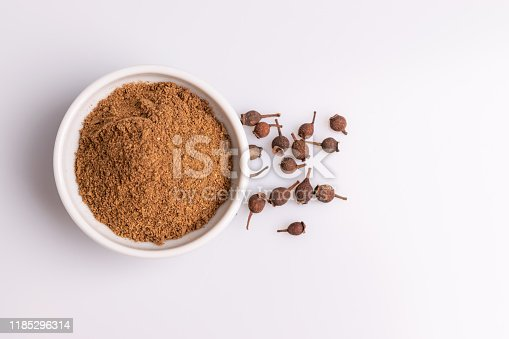 Ground allspice in white ceramic bowl isolated on white background, soft light, studio shot, copy space.  Also called Jamaica pimenta, or myrtle pepper. Latin name