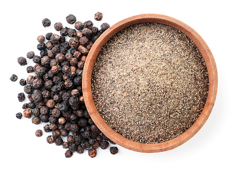 Ground black pepper in a wooden bowl and peppercorns close-up on a white background, isolated. Top view