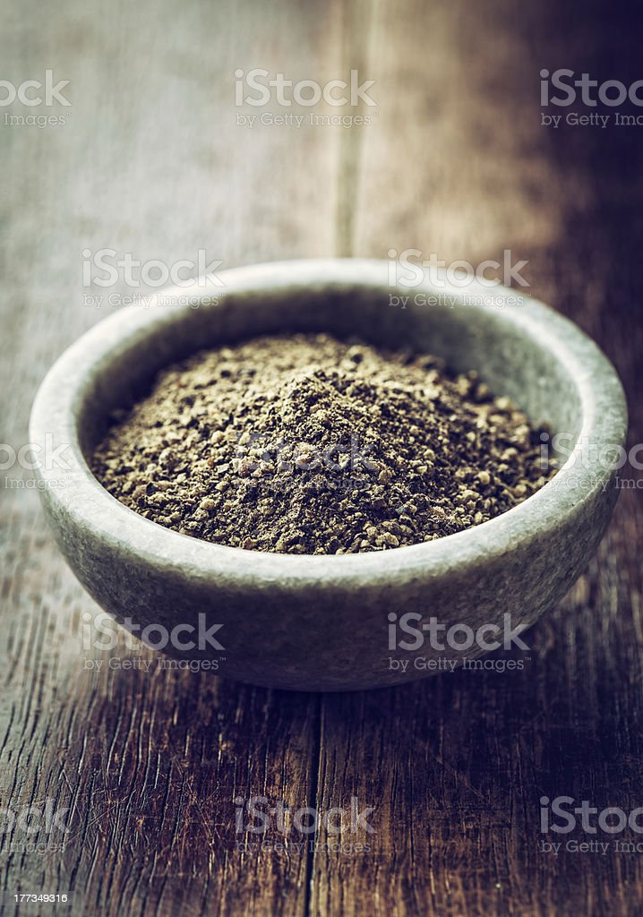 Ground black pepper in bowl on wood table stock photo