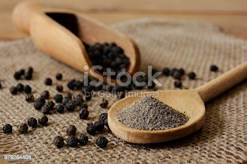 Ground Black Pepper and Peppercorns with wooden spoon and scoop.  Studio shot on June, 18, 2018