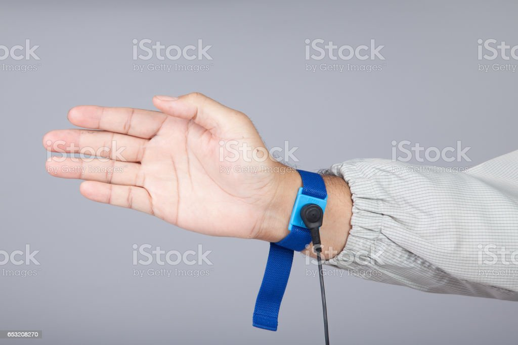 Ground bracelet on man hand wearing ESD cloth gray background. Antistatic (ESD) wrist strap or ground bracelet is an antistatic device used to safely ground a person working on electronic equipment. stock photo