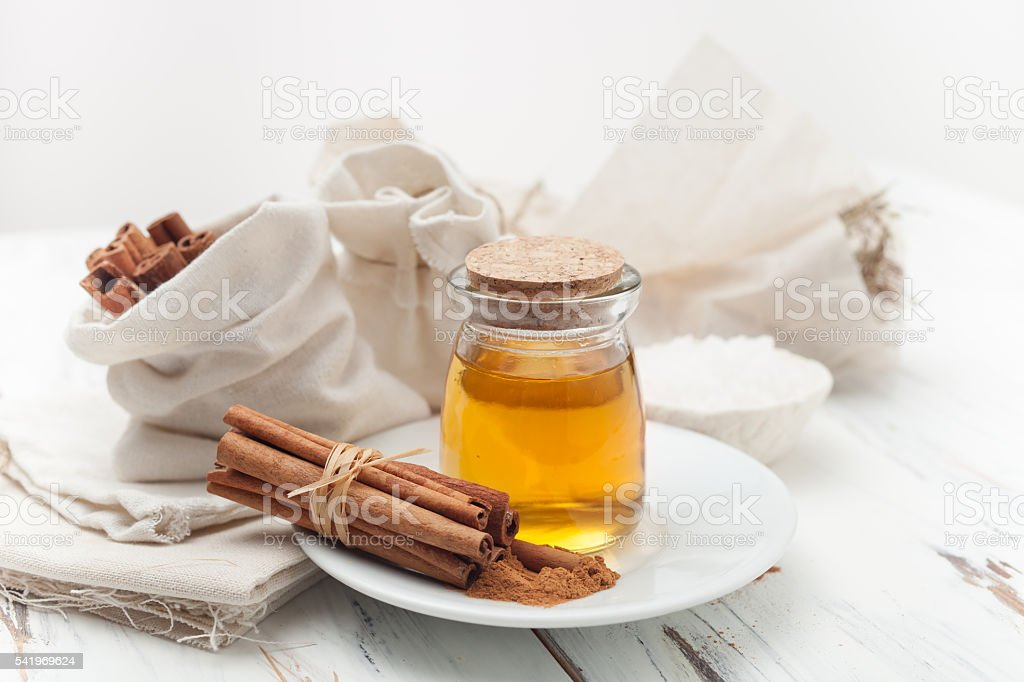 ground cinnamon, honey and cinnamon sticks on white background stock photo
