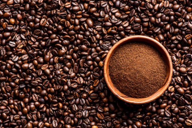 Ground coffee in bowl over coffee beans background