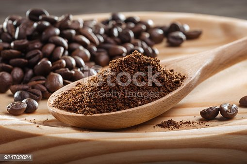 Ground coffee in wooden spoon. Coffee fried grain on wooden platter. Close-up. Coffee ground, coffee beans.