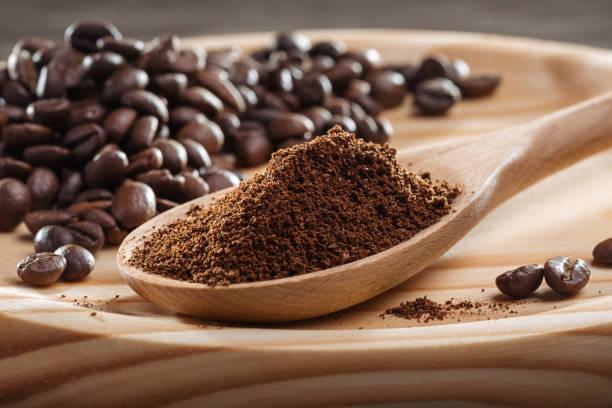 gemahlenen kaffee in löffel. kaffeebohnen. - kaffeepulver stock-fotos und bilder