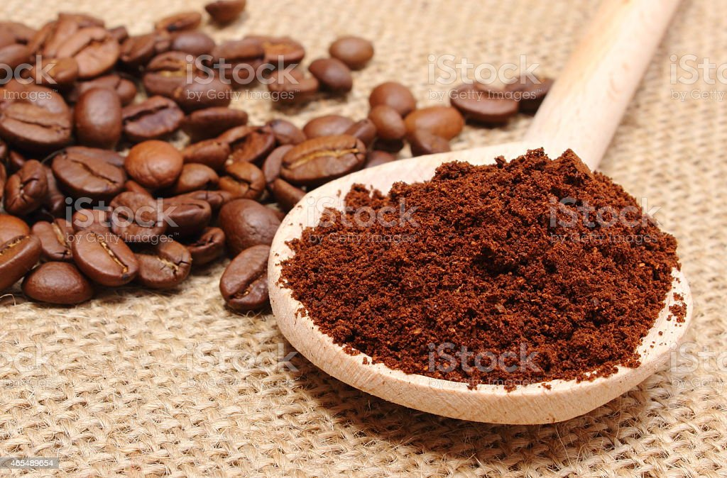 Ground coffee on wooden scoop and grains in background stock photo