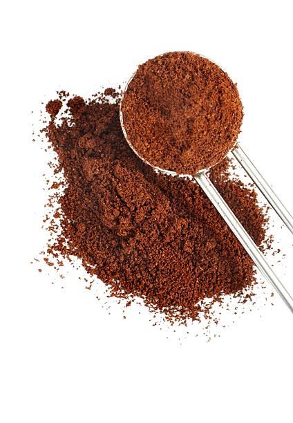 gemahlener kaffee pile mit löffel isoliert - kaffeepulver stock-fotos und bilder