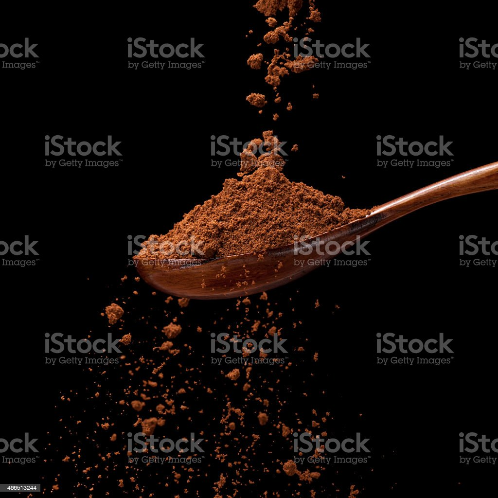 Ground coffee powder on a wooden spoon isolated on black stock photo