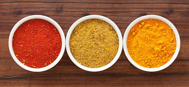 Ground condiments Three bowls containing ground spices (paprika, curry and turmeric) curry powder stock pictures, royalty-free photos & images