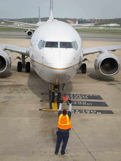 Ground crew directing jet onto ramp. stock photo