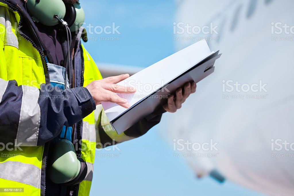 Ground crew in front of airplane Aircraft engineer holding clipboard in hands standing outdoor in front of airplane. Unrecognizable person. Adult Stock Photo