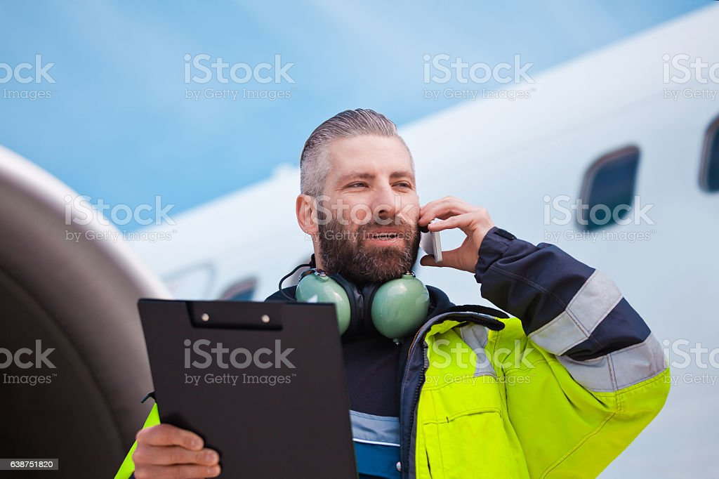 Ground crew in front of airplane Aircraft engineer holding clipboard in hands standing outdoor in front of airplane, talking on mobile phone. Adult Stock Photo