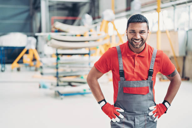 Ground crew member in the hangar Smiling airplane mechanic working in the hangar bib overalls stock pictures, royalty-free photos & images