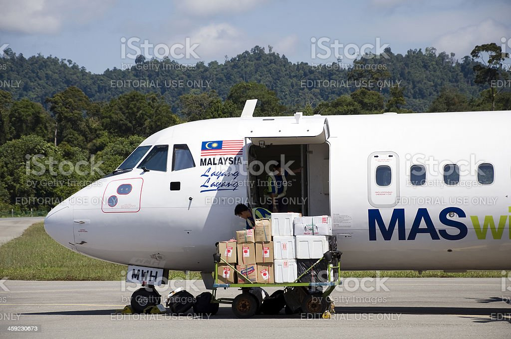 Ground crew unloading airplane royalty-free stock photo