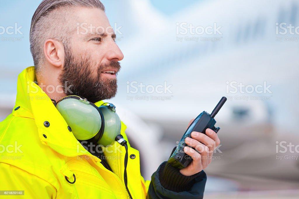 Ground crew using walkie-talkie outdoor in front of aircraft Ground crew using walkie-talkie outdoor in front of aircraft at the airport. Adult Stock Photo