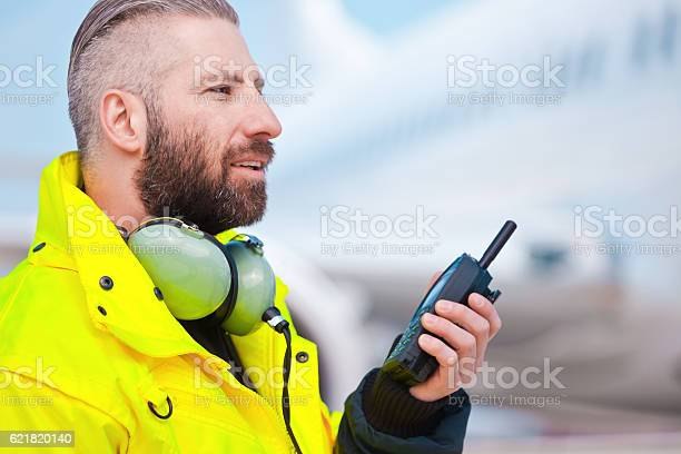 Ground Crew Using Walkietalkie Outdoor In Front Of Aircraft Stock Photo - Download Image Now