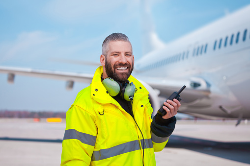 Ground crew using walkie-talkie outdoor in front of aircraft at the airport, smiling at camera.