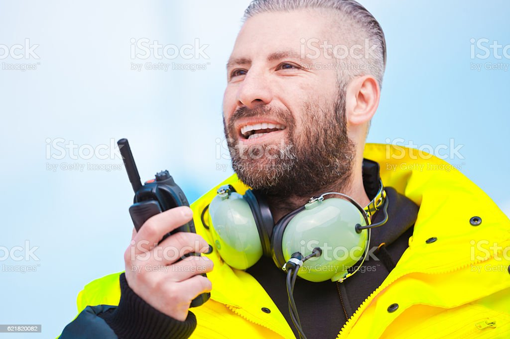 Ground crew using walkie-talkie outdoor Ground crew using walkie-talkie outdoor at the airport. Adult Stock Photo