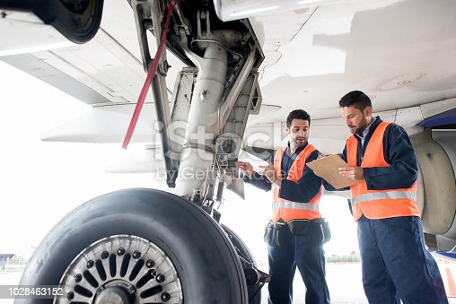Ground crew working at the airport fixing airplanes and checking the landing gear