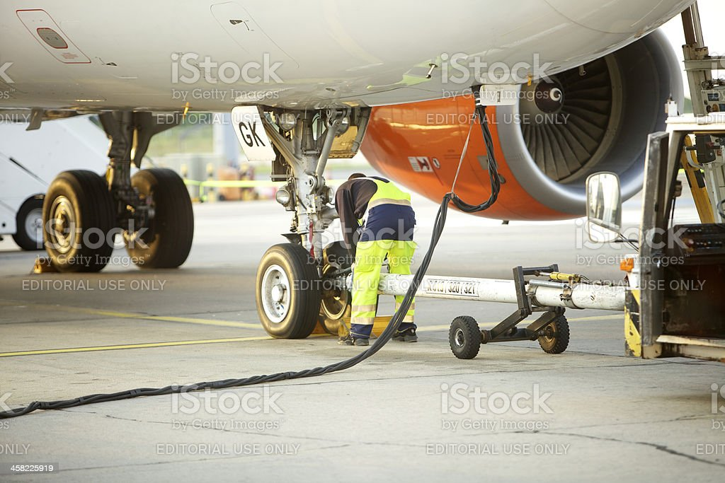 Ground crew working below a passenger airplane and refueling stock photo