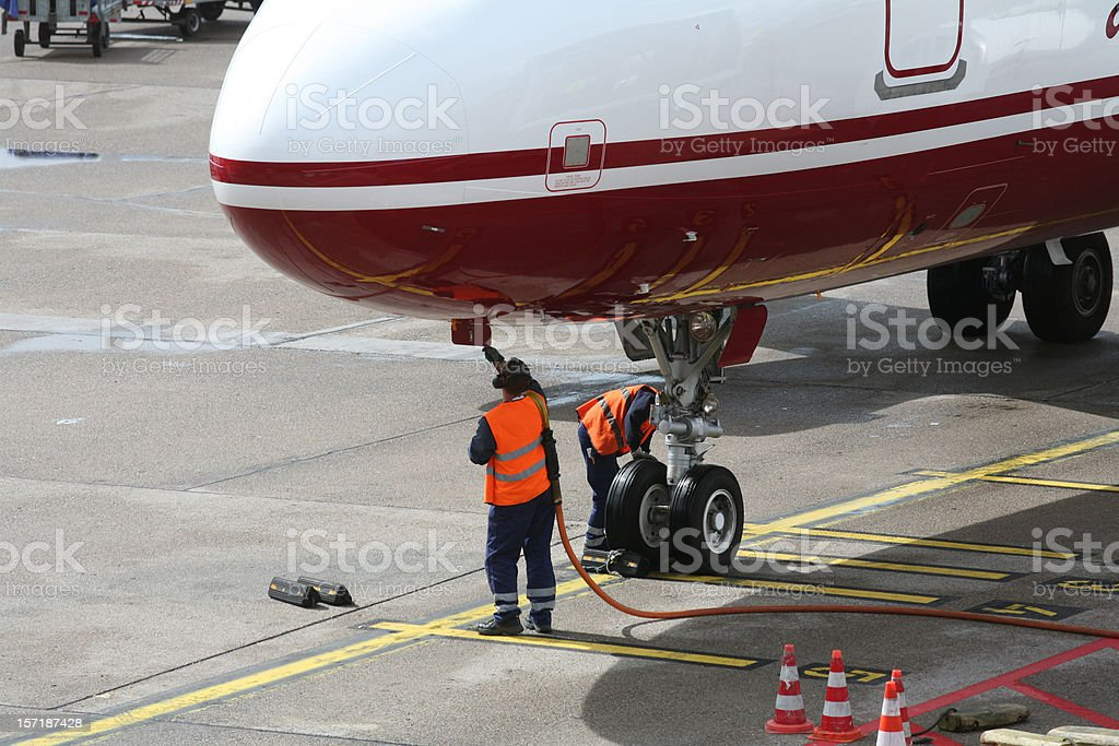 ground crew working below the cockpit of a passenger jet stock photo