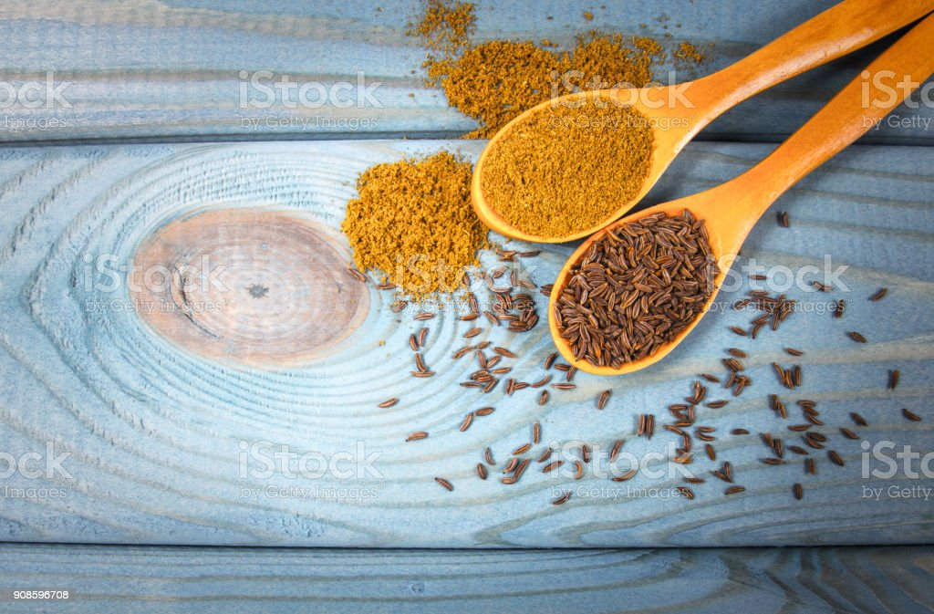 Ground cumin in a spoon and whole cumin on the wooden background. stock photo