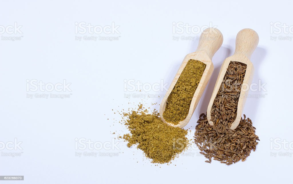 Ground cumin in a spoon and whole cumin. stock photo