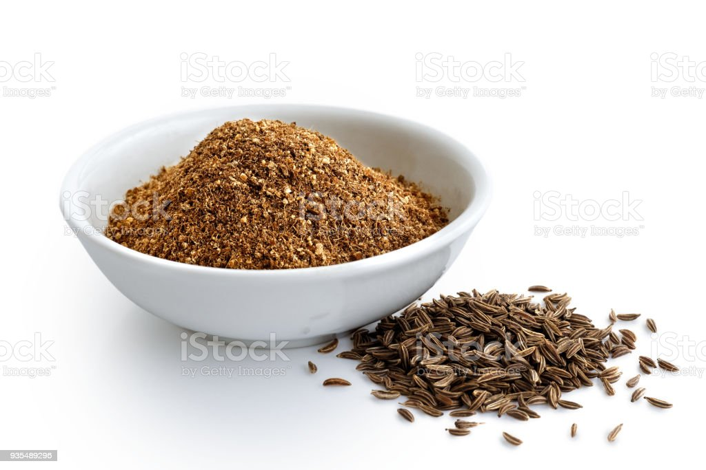 Ground cumin in white ceramic bowl isolated on white. Whole cumin. stock photo